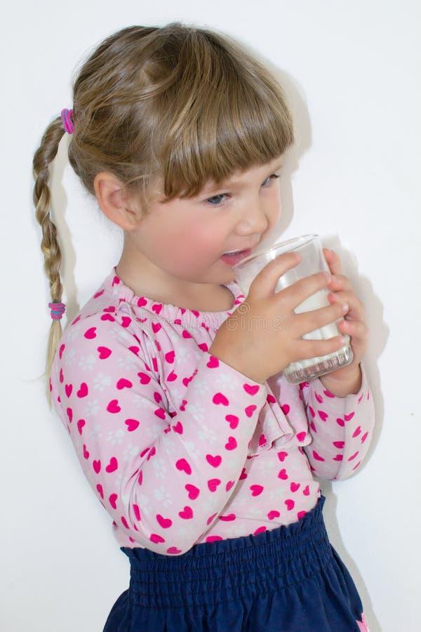 A menina bebe o leite, os benefícios do leite e o cálcio para crianças Uma criança de três anos foto de stock