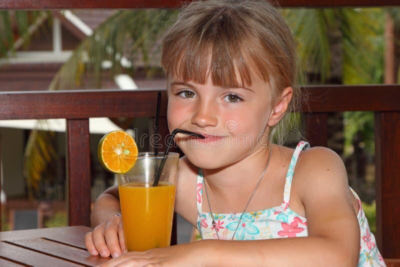 A menina bebe o sumo de laranja fotografia de stock royalty free