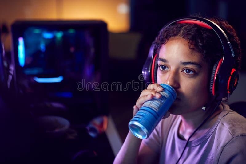 Menina Bebendo Cafeína Bebe Energia Jogando Em Casa Usando Telas De Computador Duplas À Noite fotografia de stock