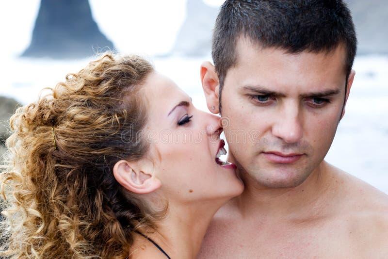 A menina beija o menino fotografia de stock royalty free