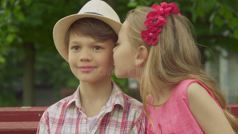 A menina beija o mordente do ` s do menino no banco imagem de stock