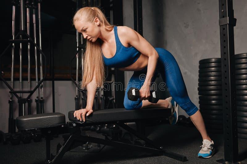 Menina bem-construída magro que levanta peso no centro de esporte imagem de stock royalty free
