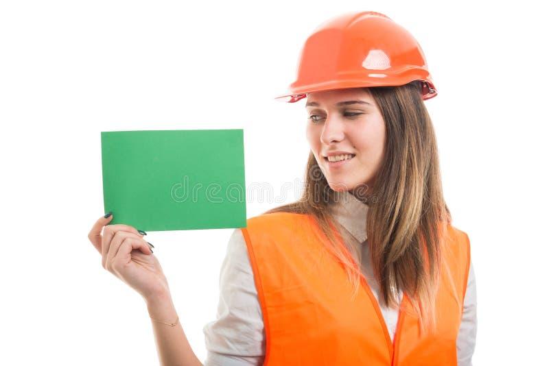 Menina bem sucedida atrativa que mostra o cartão de papel vazio imagem de stock