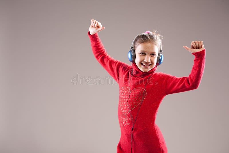Menina bem sucedida que escuta felizmente a música fotografia de stock royalty free
