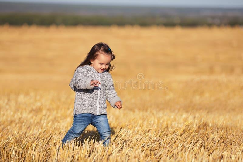 A menina bienal feliz que anda em um verão colheu o campo fotografia de stock royalty free