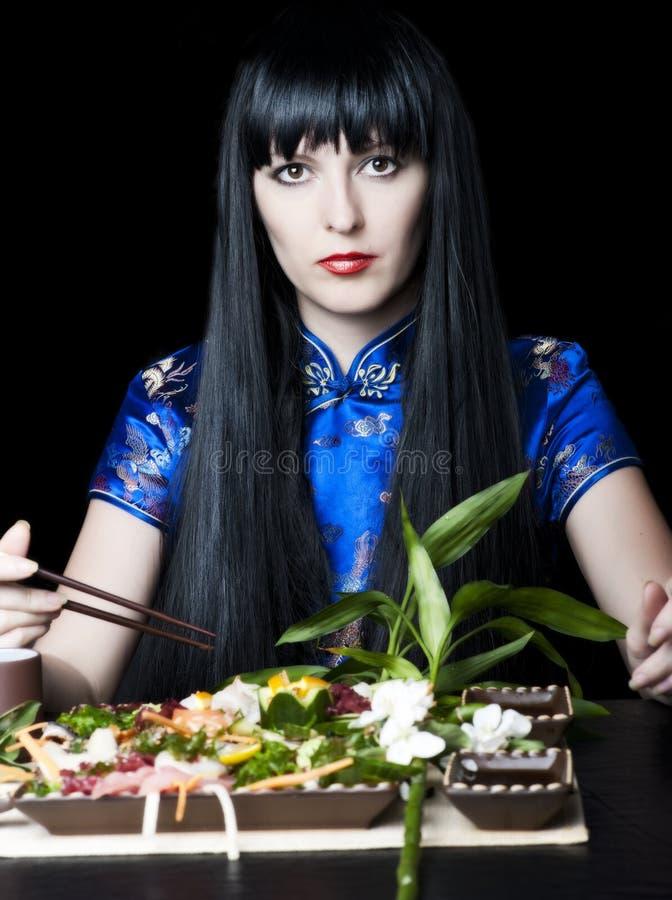 Menina Black-haired com chopsticks foto de stock royalty free