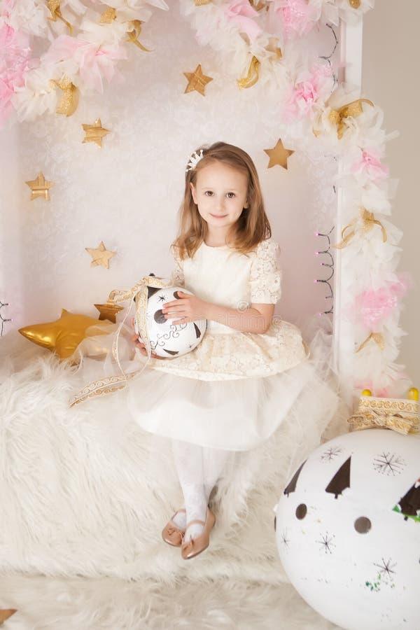 Menina blondy de sorriso bonito com uma bola grande do Natal foto de stock