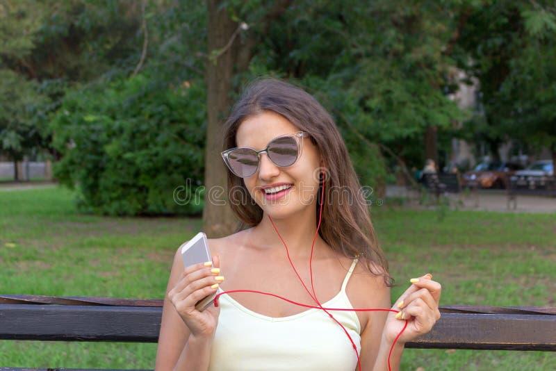A menina bonita à moda nova está escutando a música nos fones de ouvido no telefone celular A senhora está sorrindo e está tendo  imagem de stock