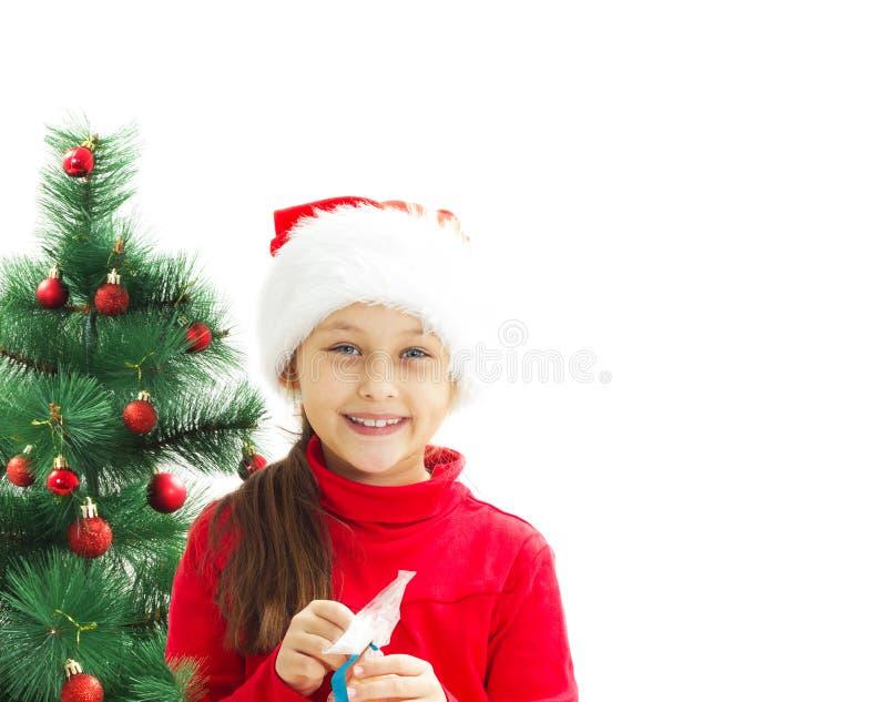 A menina bonita abre um presente do Natal fotos de stock royalty free