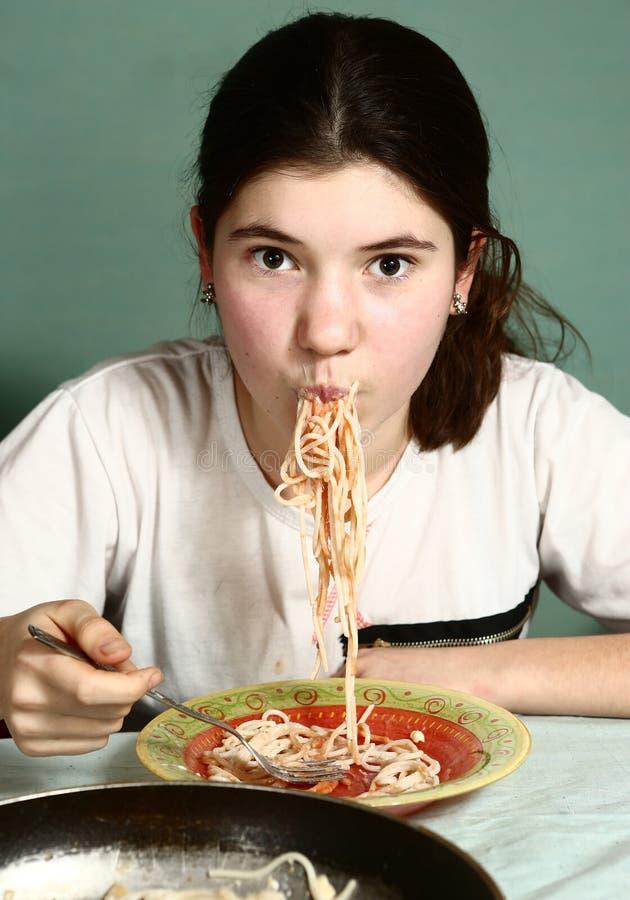 A menina bonita adolescente come os espaguetes italianos fotos de stock