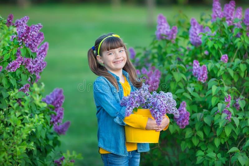 Menina bonita adorável bonito da mulher da senhora com cabelo moreno em um prado do arbusto roxo lilás Povos no desgaste das calç imagem de stock royalty free