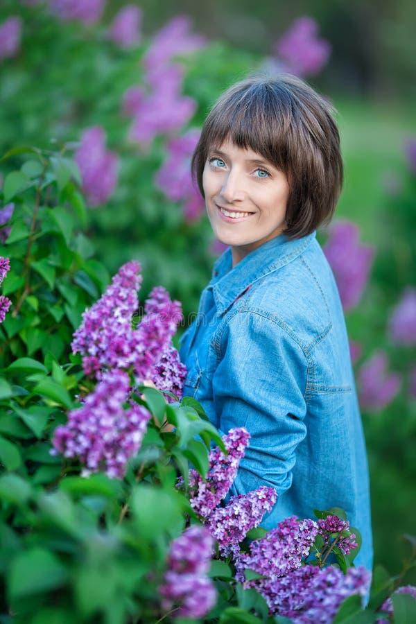 Menina bonita adorável bonito da mulher da senhora com cabelo moreno em um prado do arbusto roxo lilás Povos no desgaste das calç foto de stock royalty free