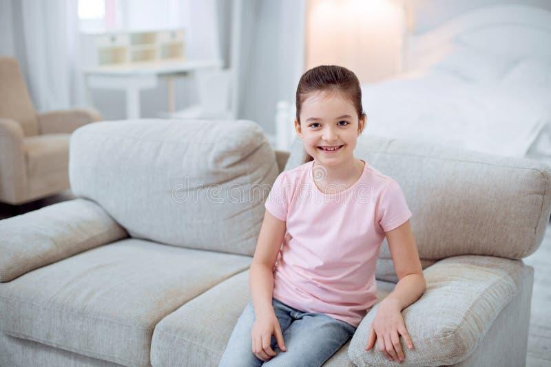 Menina bonita adorável que espera no sofá fotos de stock
