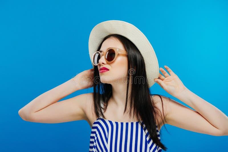 Menina bonita alegre em vidros do chapéu e de sol Sorrindo extensamente, olhando e apontando de lado Equipamento do verão Cintura fotos de stock