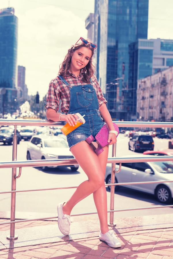 Menina bonita alegre que está perto do centro de negócios famoso que guarda seu skate foto de stock