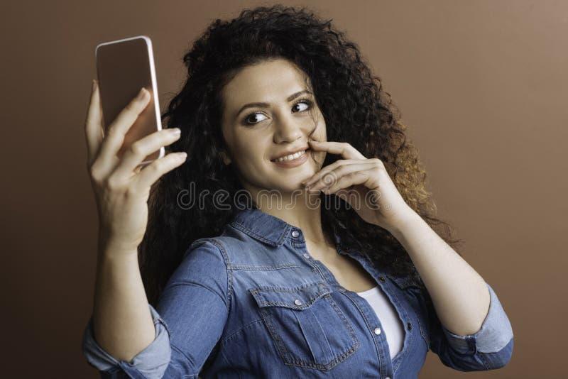 Menina bonita alegre que faz a foto em seu telefone fotografia de stock