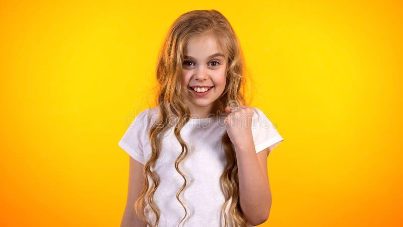 Menina bonita alegre que faz sim o gesto satisfeito com a boa propaganda do resultado imagens de stock