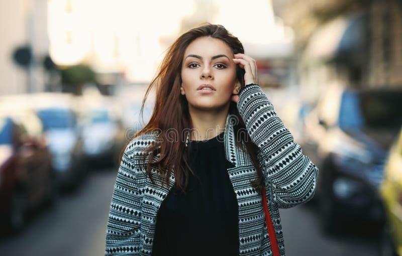 Menina bonita alegre surpreendente com cabelo moreno longo Levantamento ao ar livre Retrato ascendente próximo da escada da rua d imagem de stock