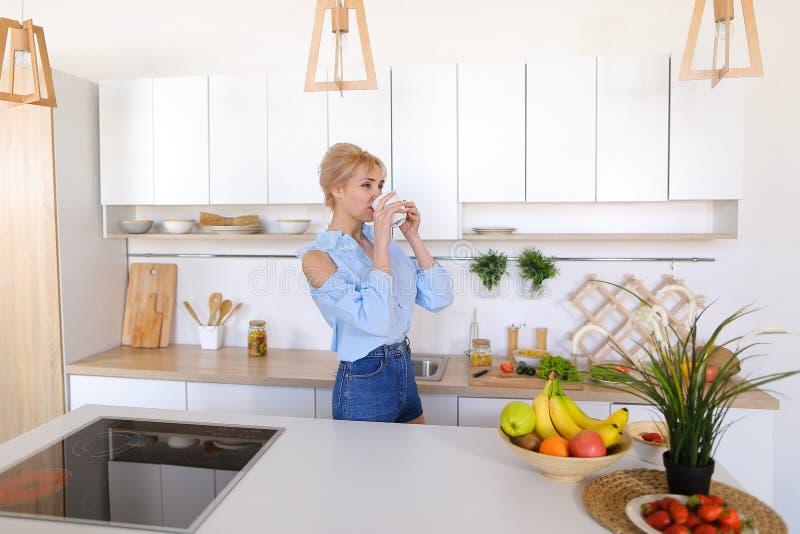 A menina bonita anda na cozinha e nos estiramentos, apreciando a manhã c imagem de stock