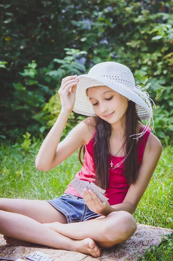 Menina bonita 10 anos velha em um chapéu branco que descansa na natureza foto de stock royalty free