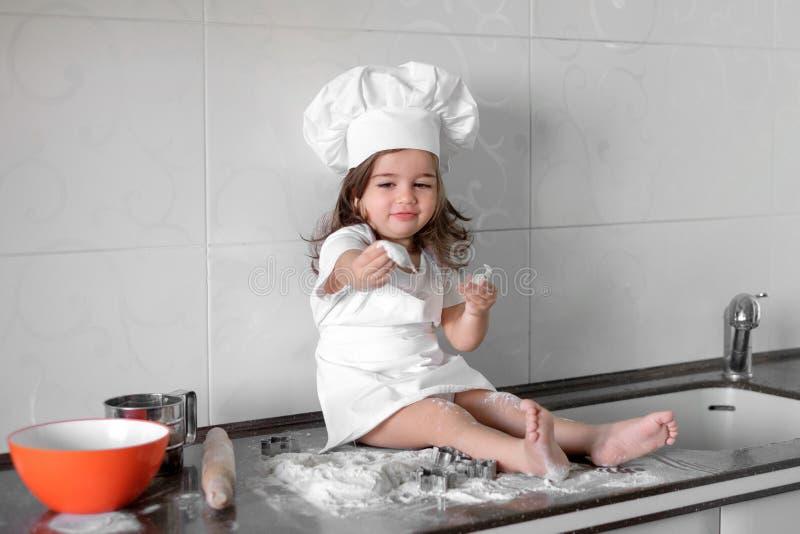 A menina bonita aprende cozinhar uma refeição na cozinha fotografia de stock
