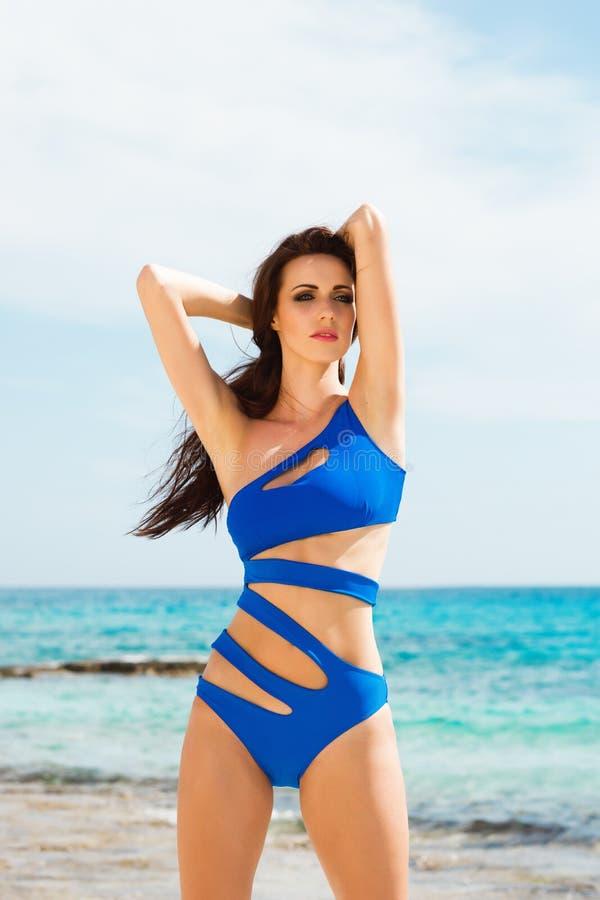 Menina bonita, apta e 'sexy' no roupa de banho azul que levanta em uma praia no verão foto de stock