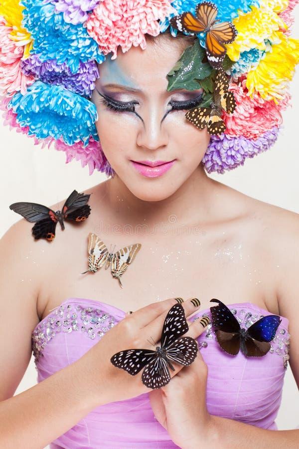 A menina bonita asiática com colorido compõe com as flores e a borboleta frescas do crisântemo foto de stock