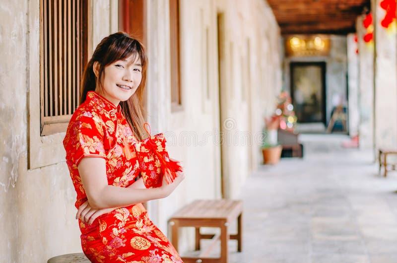 A menina bonita asiática nova no levantamento vermelho tradicional chinês do sorriso do vestido senta-se na cadeira, no ano novo  imagens de stock