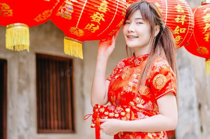 Menina bonita asiática nova no suporte vermelho tradicional chinês do sorriso do vestido perto da lâmpada da porcelana, no ano no foto de stock