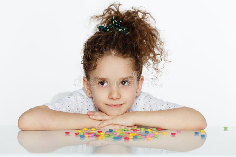 A menina bonita assentada em uma tabela, pôs seu queixo sobre suas mãos, olhando o lado um, isolado em um fundo branco fotografia de stock royalty free