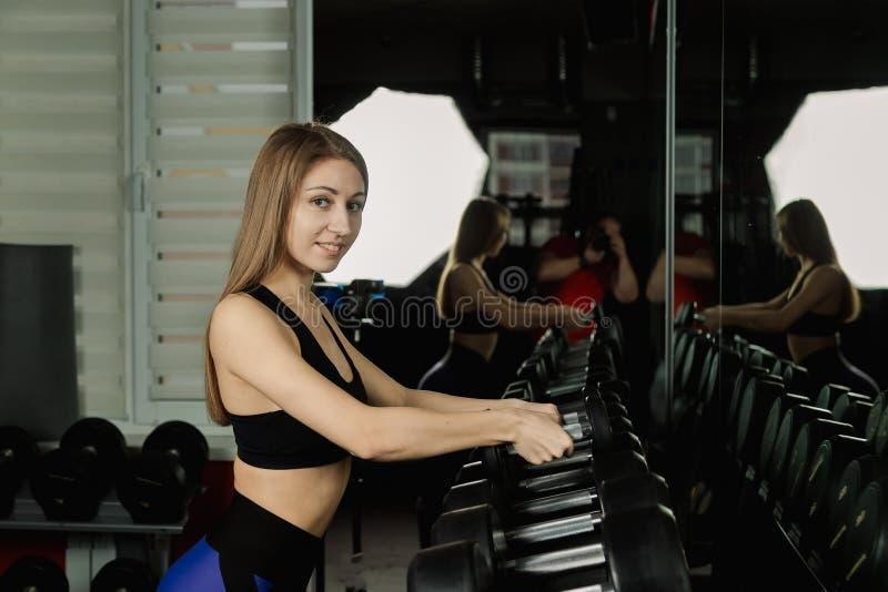A menina bonita ativa do modelo da aptidão toma pesos das cremalheiras para malhar no gym fotografia de stock