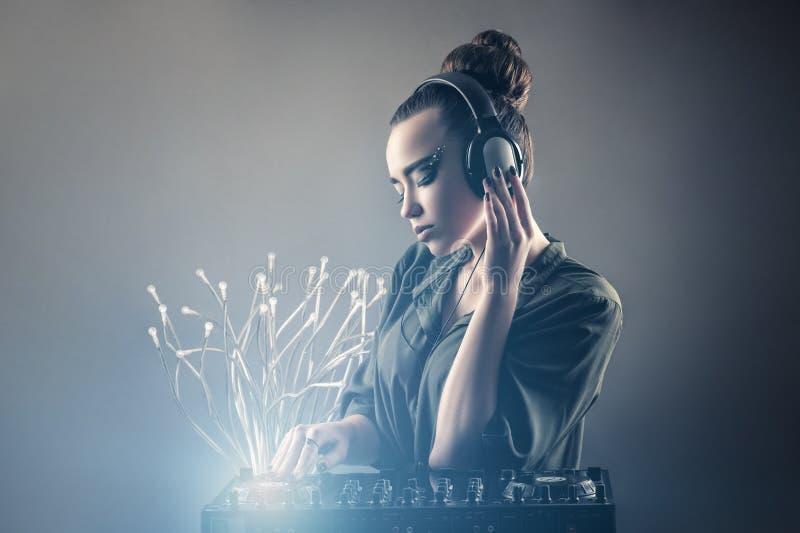 Menina bonita atrás dos telecontroles do DJ nos fones de ouvido fotos de stock royalty free