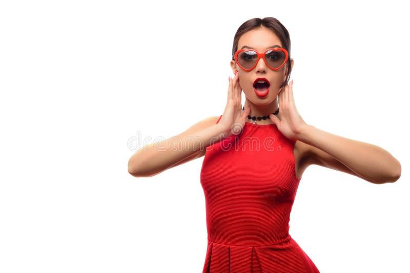 A menina bonita atrativa no vestido e em óculos de sol vermelhos na forma dos corações é boca aberta com surpresa fotos de stock