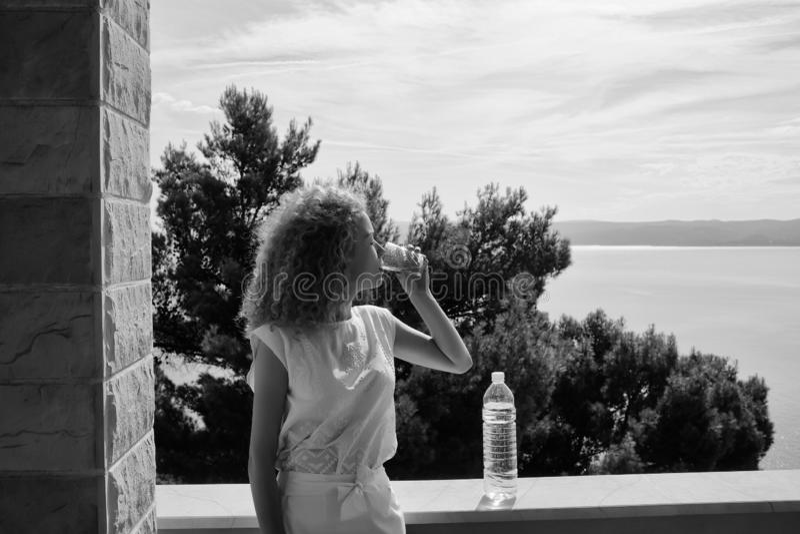 A menina bonita bebe a água foto de stock