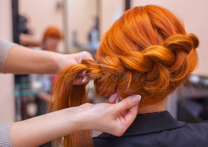 A menina bonita, cabeleireiro tece uma trança em um salão de beleza fotos de stock
