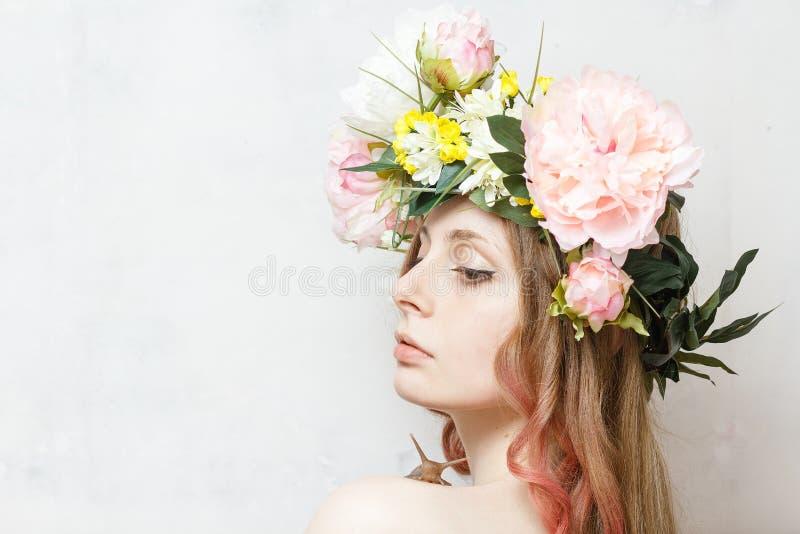 A menina bonita calma com caracol e a flor coroam foto de stock