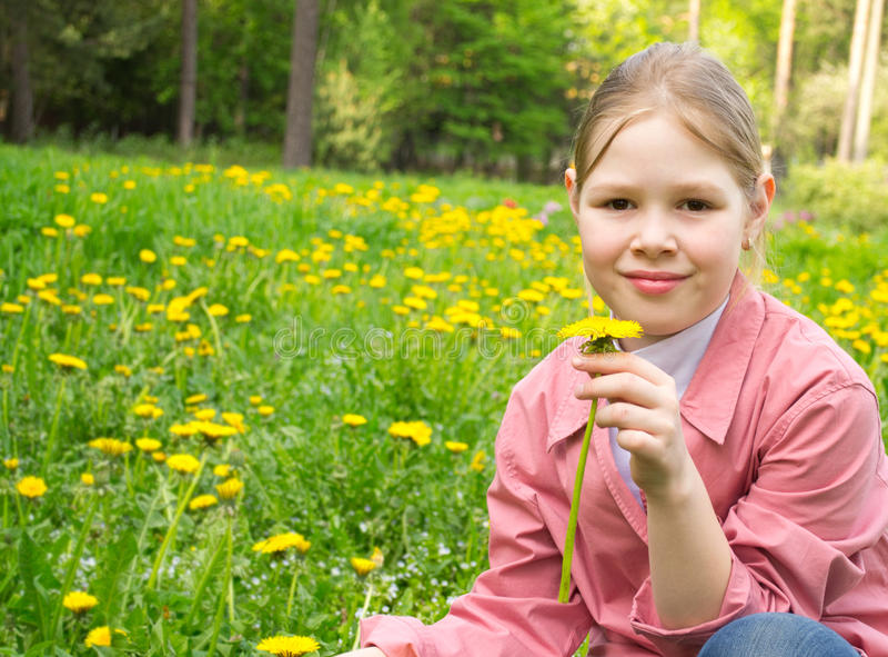 A menina bonita cheira um dente-de-leão imagens de stock
