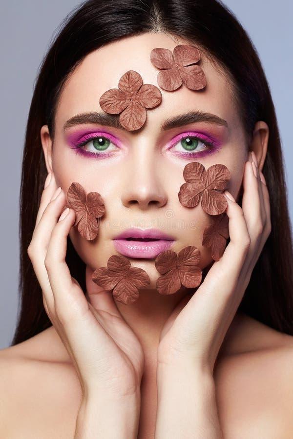 Menina bonita com as flores na cara foto de stock