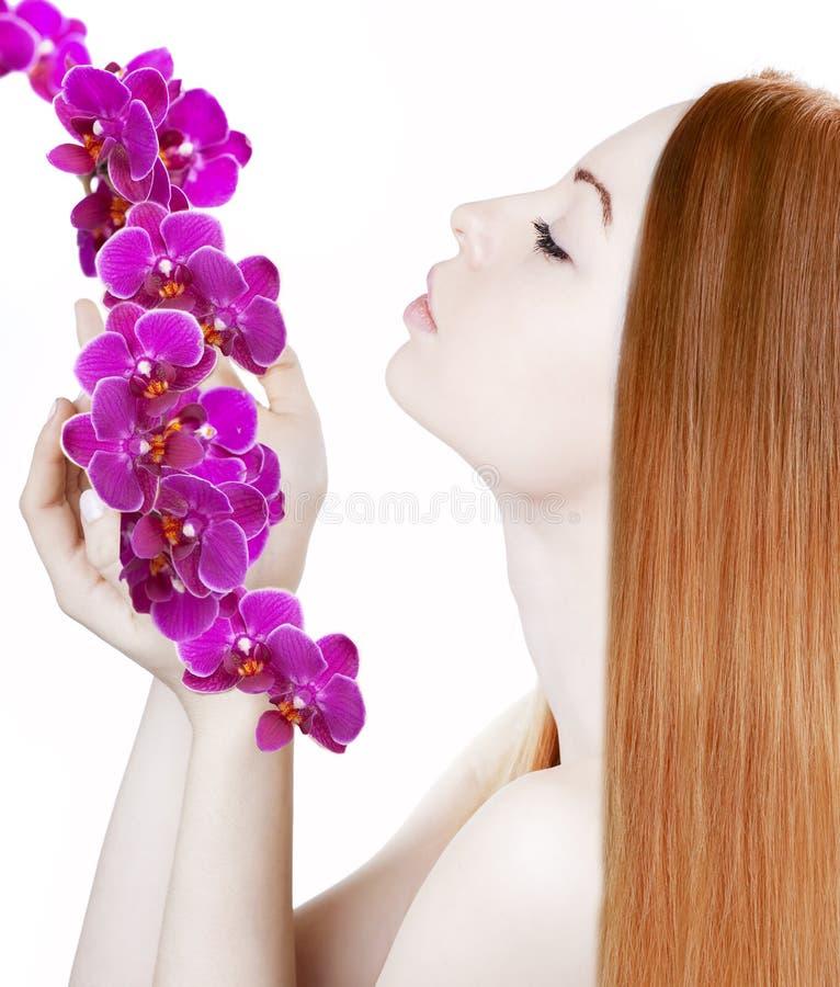 Menina bonita com as orquídeas em seu cabelo lindo imagem de stock