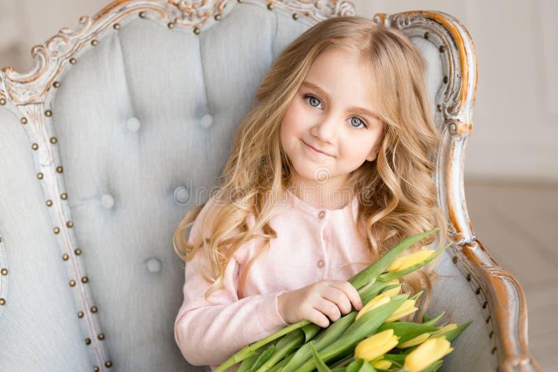 Menina bonita bonita com as tulipas amarelas das flores que sentam-se na poltrona, sorrindo Foto interna imagem de stock