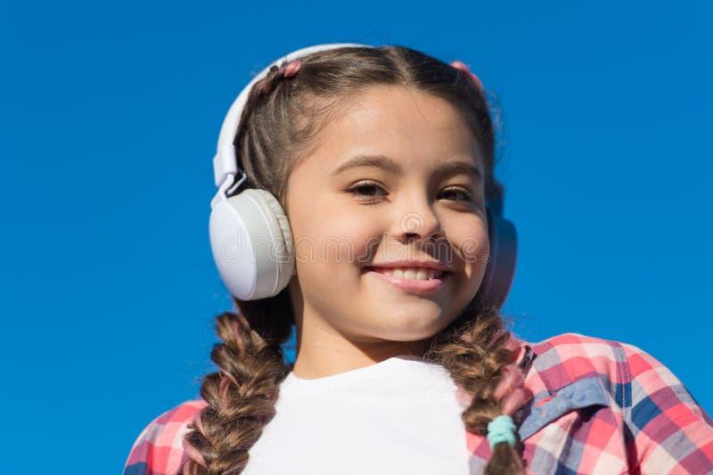 Menina bonita com auscultadores A menina feliz nova está escutando a música Melômano à moda Sorriso feliz na cara da menina fotos de stock