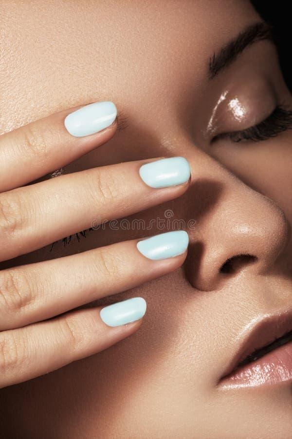 A menina bonita com azul prega o tratamento de mãos, pele limpa foto de stock royalty free