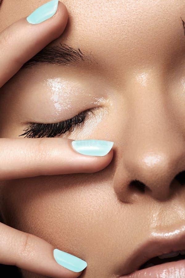 A menina bonita com azul prega o tratamento de mãos, pele limpa fotografia de stock