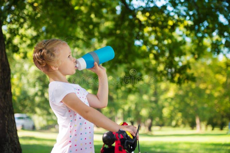A menina bonita com bicicleta bebe a água no parque do verão foto de stock