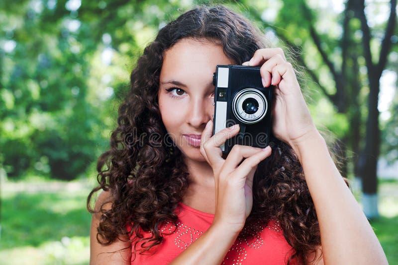 Menina bonita com a câmera velha do lomo do filme exterior foto de stock
