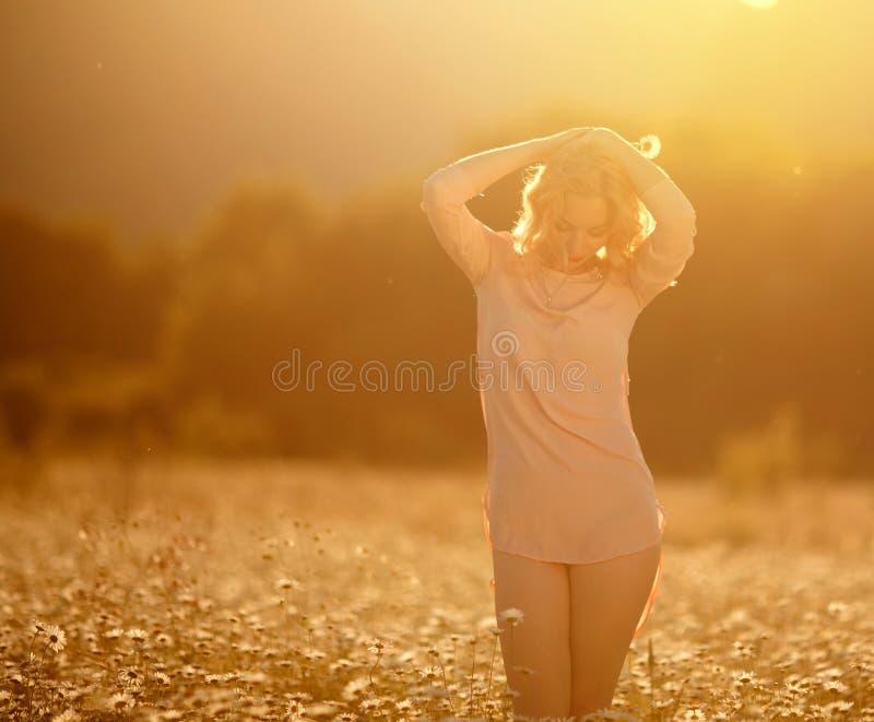 A menina bonita com cabelo branco aprecia um campo das margaridas imagens de stock
