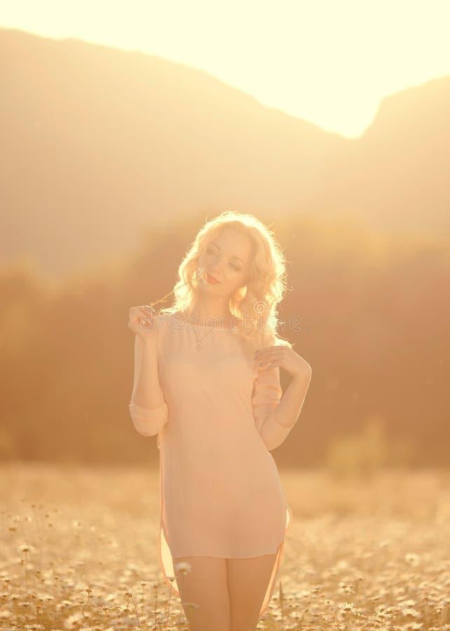 A menina bonita com cabelo branco aprecia um campo das margaridas fotos de stock royalty free