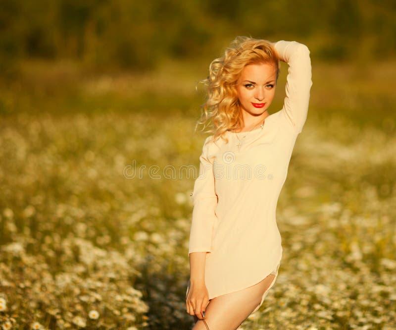 A menina bonita com cabelo branco aprecia um campo das margaridas imagem de stock