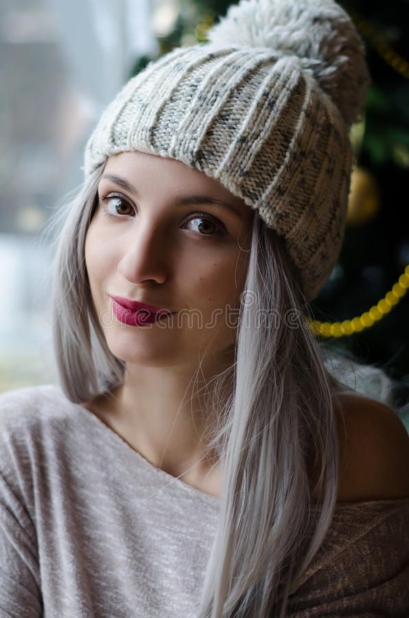 Menina bonita com cabelo do cinza de prata no chapéu do pom do pom com os bordos do vermelho de vinho no inverno fotos de stock