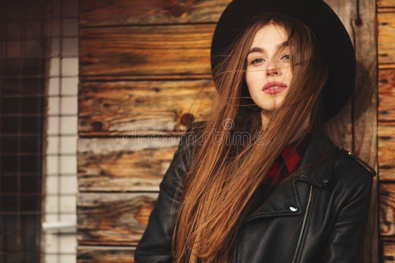 Menina bonita com cabelo e o chapéu negro longos, suportes no fundo da casa de madeira velha do vintage fotografia de stock